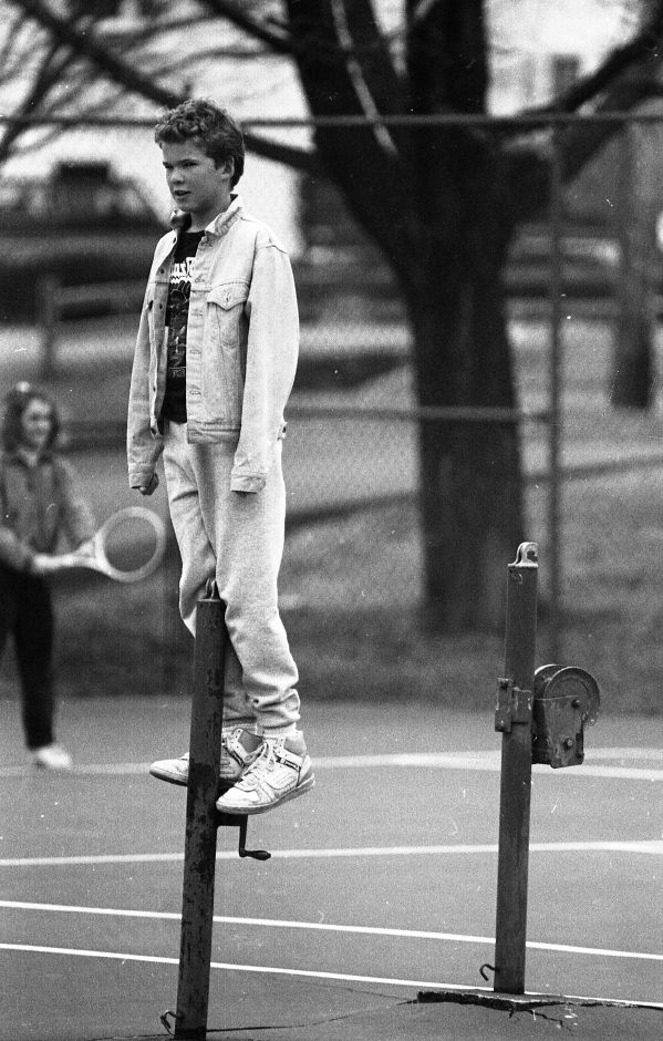RJ file photo - Rick Warner, 13, stands on one of the poles that holds the net at the Doolittle Park tennis court Feb. 23, 1989. He was watching friends pla a game of tennis using raquetball equipment.