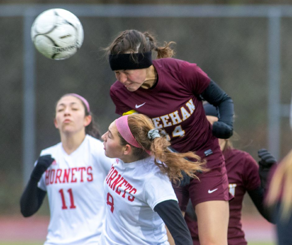 Sheehan's Olivia Dubuc goes over Branford's Alayna Boileau to redirect a corner kick on net during the first round of the 2019 Class L state tournament. Dubuc, a two-time All-State Class L player, finished her career with 71 goals, second most in Sheehan girls soccer history. Aaron Flaum, Record-Journal