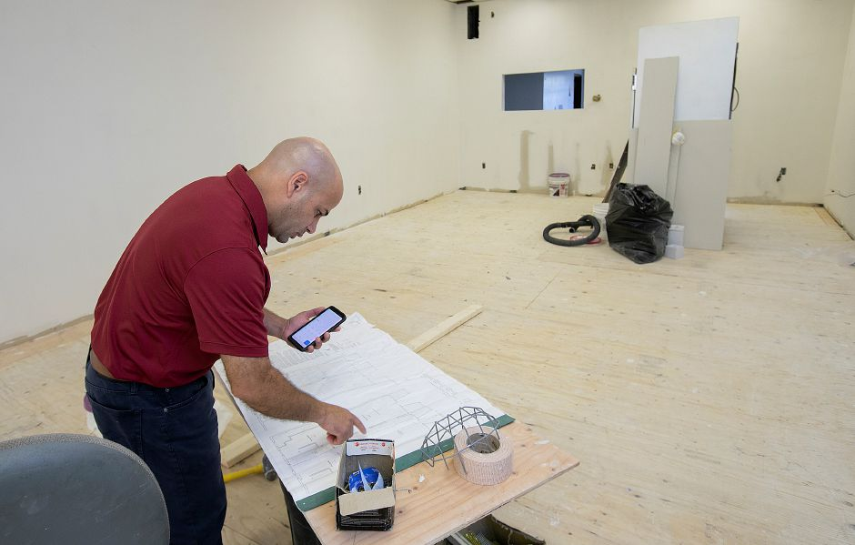 Miguel Castro, a city councilor and owner of Prestige Construction, looks over plans for construction of a new dining area for La Poblanita Grocery & Deli at 41 Colony St., Thurs., Aug. 15, 2019. Prestige Construction is the general contractor for the project. Dave Zajac, Record-Journal