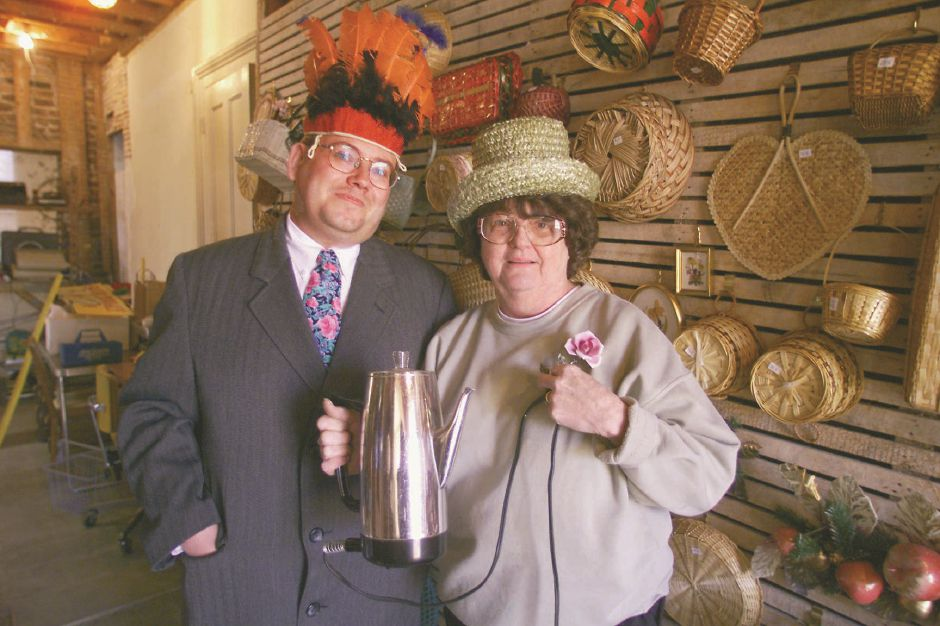 RJ file photo - Jerry Farrell Jr., left, head of the Wallingford Historic Preservation Trust, and Regina Banaszweski will have an estate sale at the Johnson Museum in Wallingford, March 1999. The hats and percolator are among the items for sale.