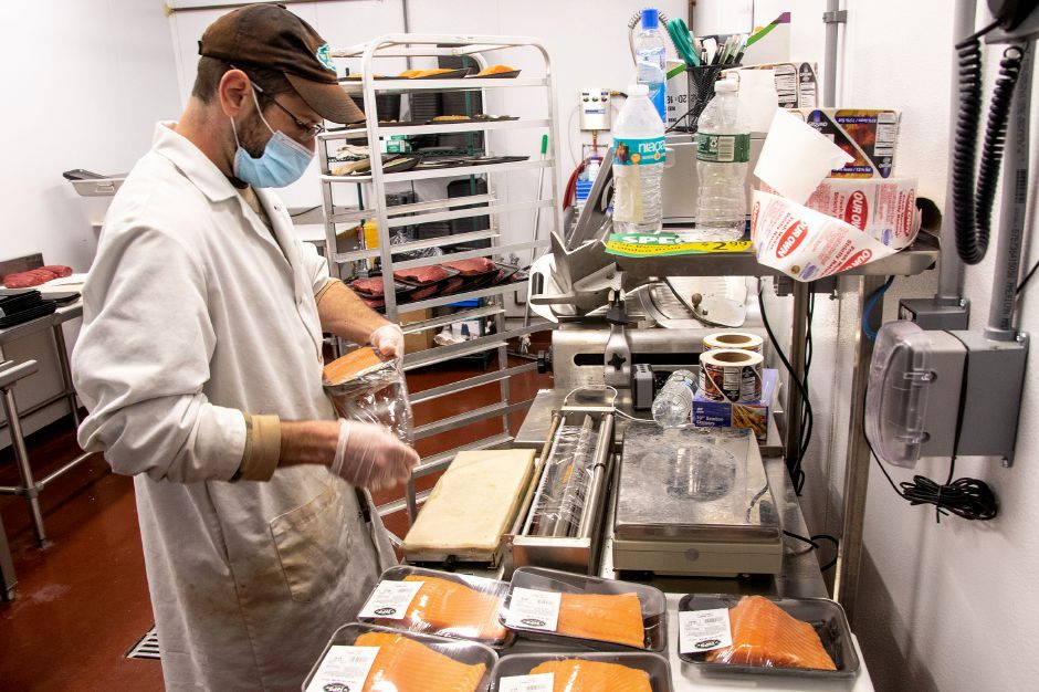 Tops Marketplace butcher Ben Cossette, packages salmon filets as he gets them ready for sale at the Southington store on Tuesday, June 30, 2020. Aaron Flaum