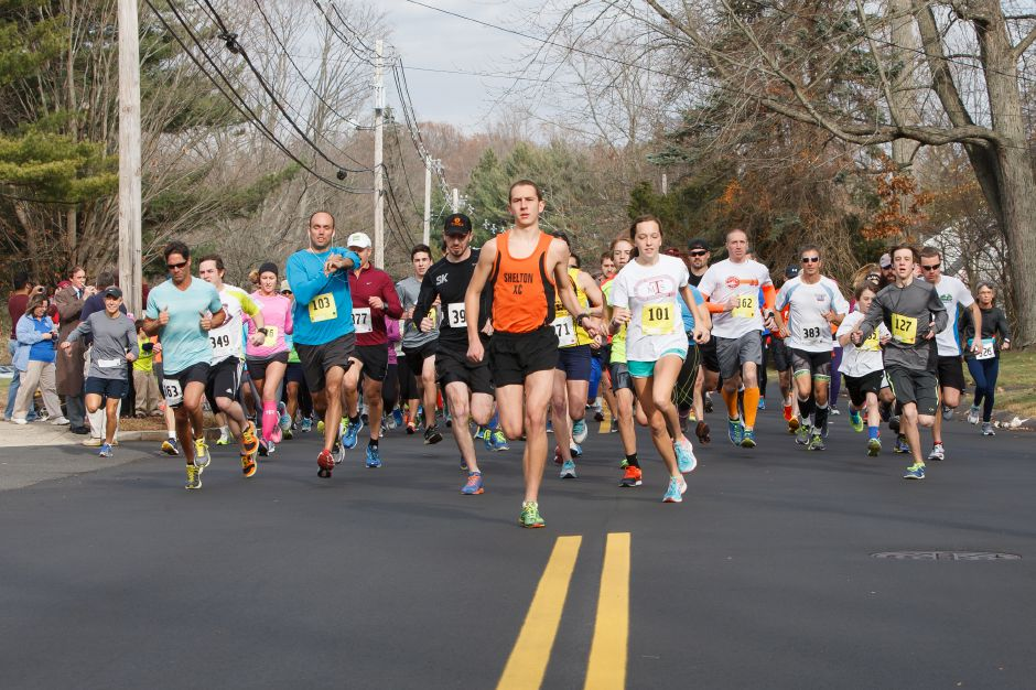 Joe Edelstein of Shelton in orange and Elizabeth Fengler (101) of Wallingford lead the start Sunday during the Wallingford Turkey Trot held at Stevens Elementary School in Wallingford Nov 23, 2014 | Justin Weekes / For the Record-Journal