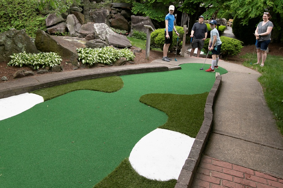 Jason Kalwat, 11, of Plantsville, just misses a hole-in-one while celebrating his birthday with brother Brian, 13, left, and parents Doug and Jamie at the newly rebuilt Hidden Valley Miniature Golf in Southington Friday.