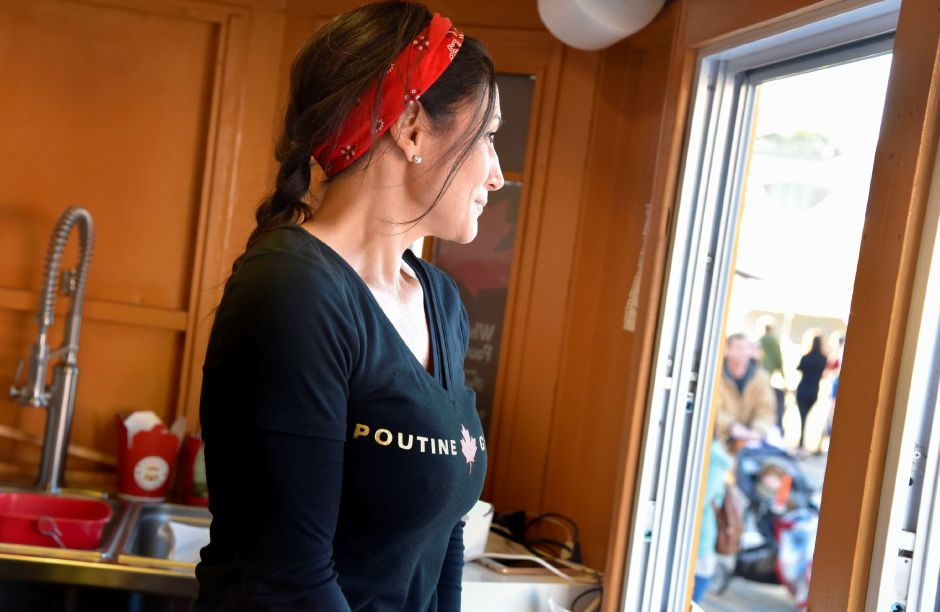 Lisa Greene watches the Apple Harvest Festival in Southington getting started, from inside the Poutine Gourmet food truck, on Oct. 4, 2019. | Bailey Wright, Record-Journal