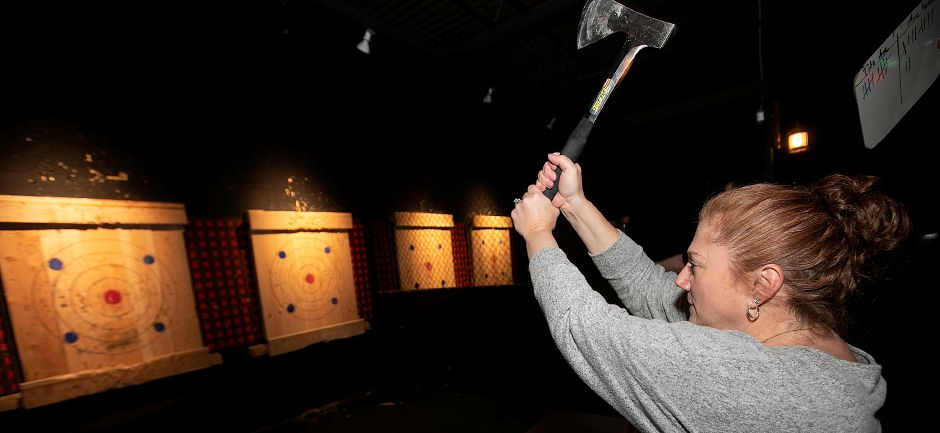 Tammy Evans, of Oakdale, takes aim during a group competition at Montana Nights Axe Throwing in Newington, Thursday night. Montana Nights will be opening another location in the Factory Square building in Southington. Photos by Dave Zajac, Record-Journal
