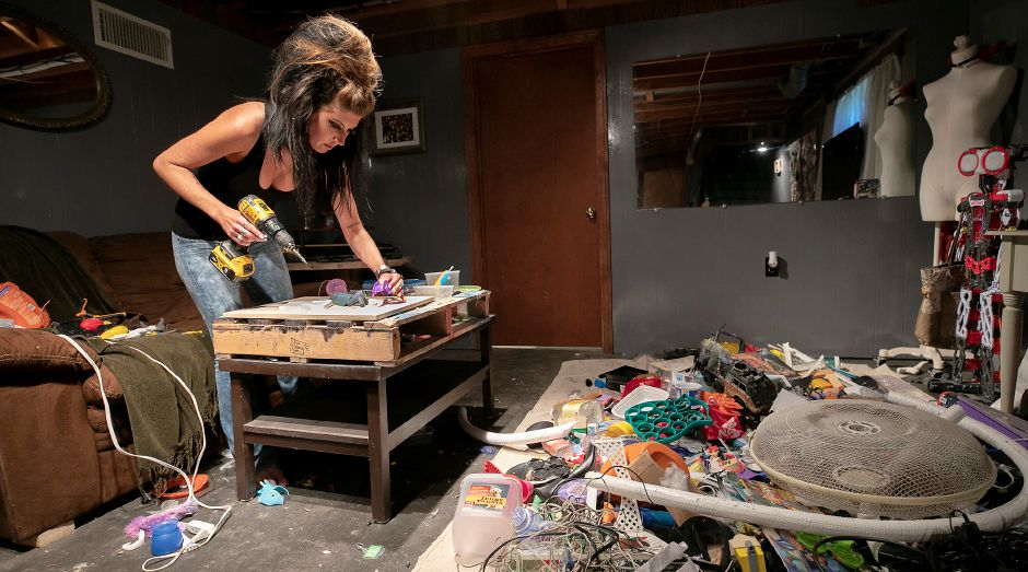 Hongo starts a new trash sculpture using mostly discarded plastic from a large pile in her basement. Hongo, a studio manager at Art Studio of Connecticut on West Street, creates works of art from a variety of discarded trash, recyclables and found objects.