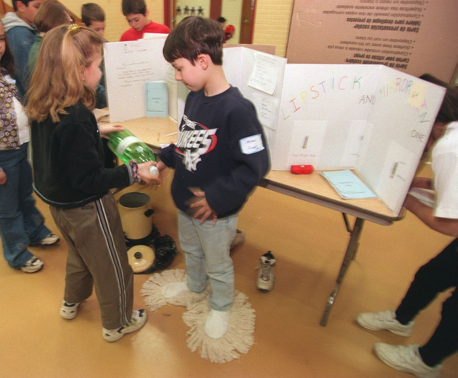 RJ file photo - Arrilynne Ala, left, prepares her invention, the bottle fountain for watering plants, while standing next to fourth-grade classmate Michael Knobb, who is wearing his invention, the sock mop, during a recent science fair at Parker Farms School in Wallingford, Feb. 1999.