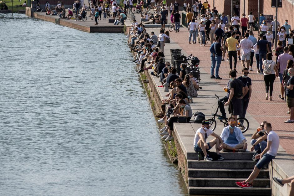 People relax at the Naviglio Grande canal, in Milan, Italy, Sunday, May 24, 2020. Europeans and Americans soaked up the sun where they could, taking advantage of the first holiday weekend since coronavirus restrictions were eased, while European governments grappled with how and when to safely let in foreign travelers to salvage the vital summer tourist season. Italy, which plans to open regional and international borders on June 3 in a bid to boost tourism, is only now allowing...