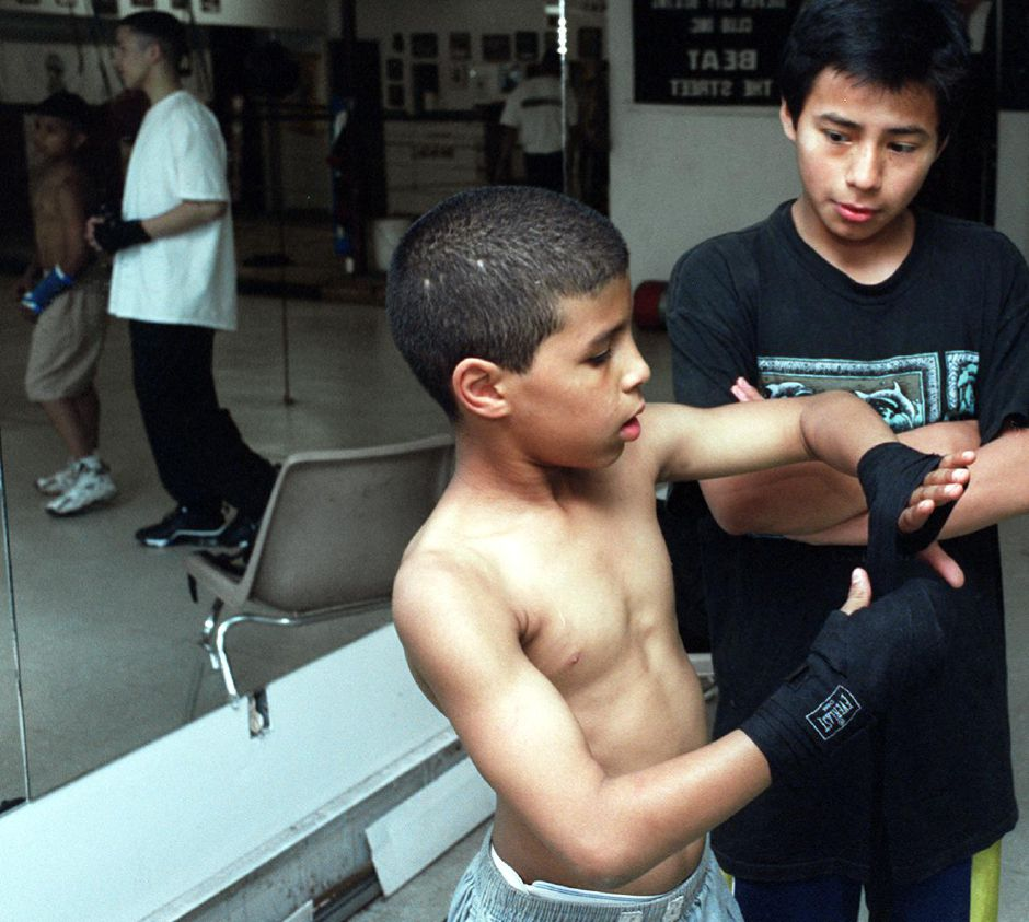 Edwin Otero,11 wraps his hands with cloth as he gets ready to box. Next to him Willy Morales, also a member of the Silver City Boxing Club June 15, 2000.