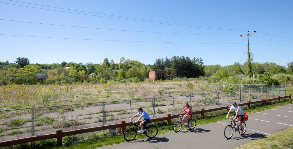 Bicyclists pedal past the former Ideal Forging site along the Farmington Canal Heritage Trail in Southington, Wed., May 20, 2020. Owners of the site are hopeful about an upcoming auction for the 14-acre property. Dave Zajac, Record-Journal