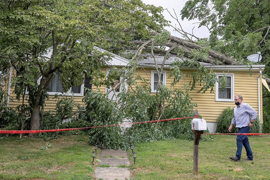 A man walks by a fallen tree on a home on Parkview St. in Meriden Tuesday as Tropical Storm Isaias moved through the region. Photos by Dave Zajac, Record-Journal