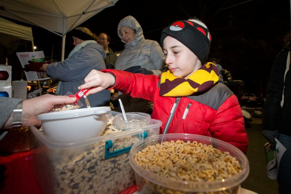 Carter Smith 8 of Southington spoons out grain cereal for Santa