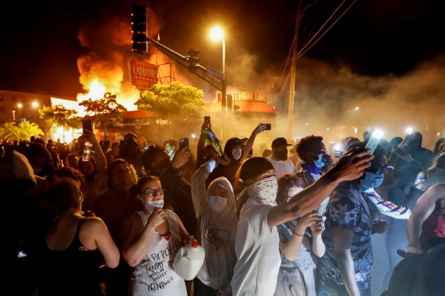 Protestors demonstrate outside of a burning liquor store near the Minneapolis 3rd Police Precinct, Thursday, May 28, 2020, in Minneapolis. Protests over the death of George Floyd, a black man who died in police custody Monday, broke out in Minneapolis for a third straight night. (AP Photo/John Minchillo)