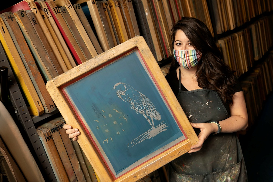 Rachel DeCavage, owner of Cinder + Salt, shows one of her screen printing designs of a heron Tuesday at the 520 Main St. business in Middletown. DeCavage is moving to a different storefront in Middletown and transferring the production side of her business to 115 Water St. in Southington. Cinder + Salt produces clothing and accessories in a zero-waste print shop. Dave Zajac, Record-Journal