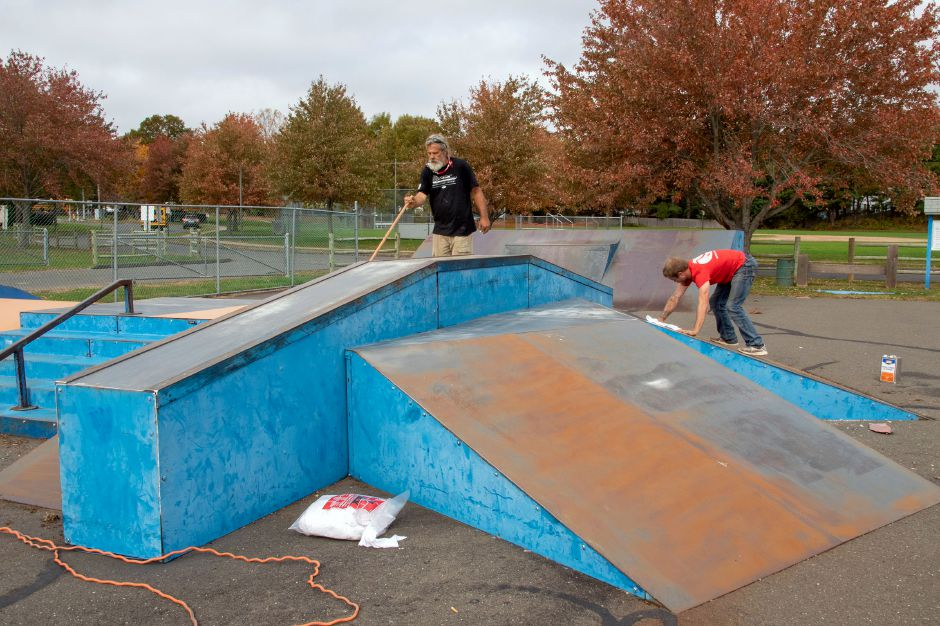 Top: American Ramp Company's Mike Fordyce, left, and Colby Etcheson work on resurfacing the ramps at the Cheshire Skate Park at Bartlem Recreation Area  Tuesday. The skate park is going to be closed until Friday for refinishing. Bottom left: Mike Fordyce  resurfaces the ramps. Bottom right: Colby Etcheson cleans off one of the ramps so it can be resurfaced.
