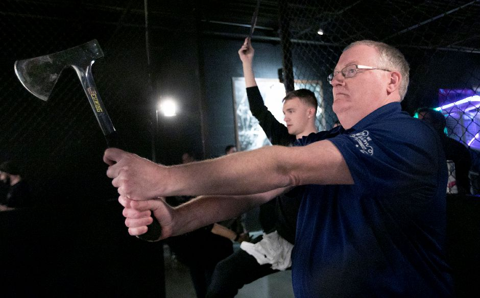 Scott Buddle, of Prospect, takes aim as instructor Kam Kuziora signals the start of a group competition at Montana Nights Axe Throwing in Newington on Thursday.
