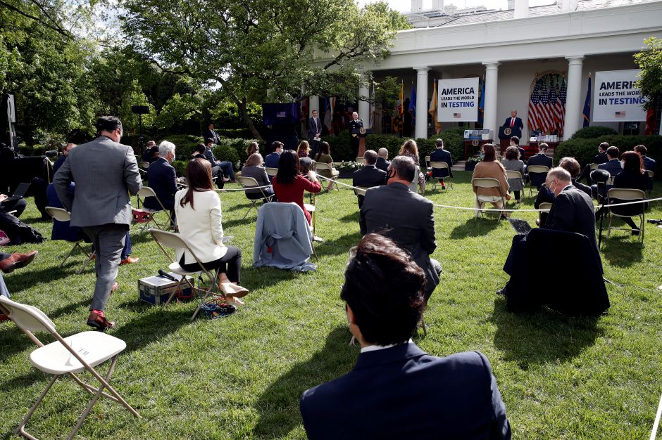 A reporter approaches a microphone to ask as question of President Donald Trump during a briefing about the coronavirus in the Rose Garden of the White House, Monday, May 11, 2020, in Washington. (AP Photo/Alex Brandon)
