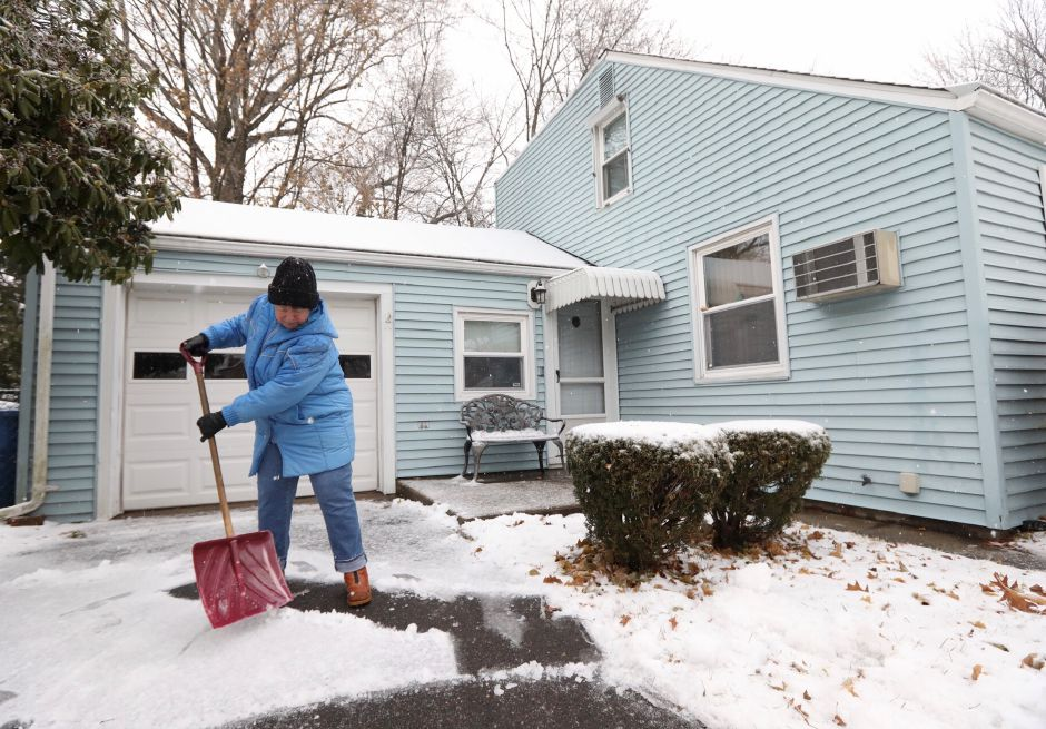 Sharon Beegan, of Meriden, clears snow and ice from the driveway of her Wall Street residence, Mon. Dec. 2, 2019. | Dave Zajac, Record-Journal