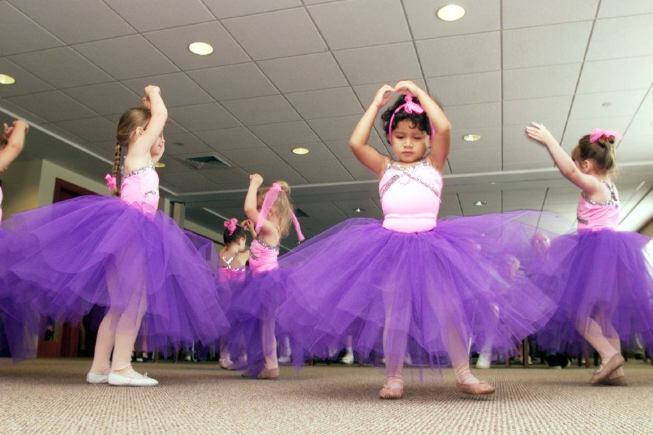 Rachel Conte, left, 4, and Shannon Sullivan, center, 3, dance with their Miss Joyce
