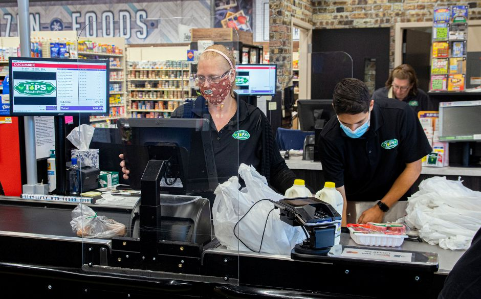 Above left: Cashier Becky Reopel works behind a piece of plexiglass as Jared Rivera bags groceries for Mike Rogers of Southington, at Tops Marketplace on Tuesday. The plexiglass was installed to protect the cashiers from the spread of Covid-19.