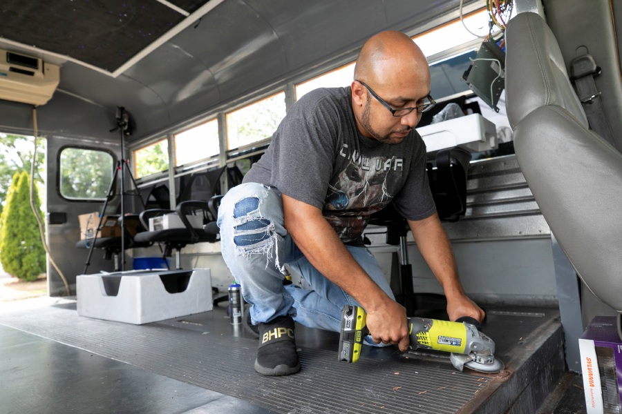 Artist Apollo Maldonado, of Meriden, owner of All Sketched Out LLC, grinds down a bolt while refurbishing a retired school bus to create a mobile art studio in Meriden, Tues., Aug. 11, 2020. Maldonado had to close his Colony Street pop up art studio due to the Covid-19 pandemic. Dave Zajac, Record-Journal