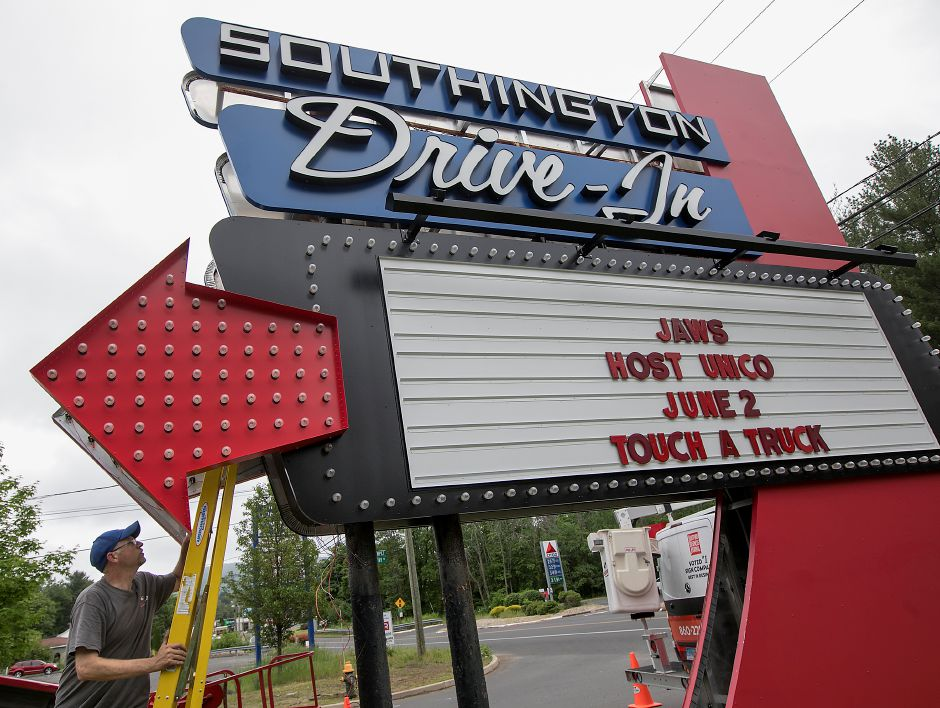 Crews from Sign Pro install the new Southington Drive-In sign on June  2018. Dean Dube, installer, climbs a ladder to access electrical wiring inside the marquee.