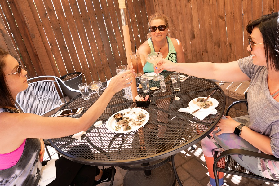 Customers, left to right, Wondeline Colon-Rivera, Darby Bronson and Lisa Kelsey, all of Cheshire, enjoy a group toast on the patio of the Hop Haus, 28 W. Main St. in Plantsville, Thurs., Jun. 25, 2020. Dave Zajac, Record-Journal