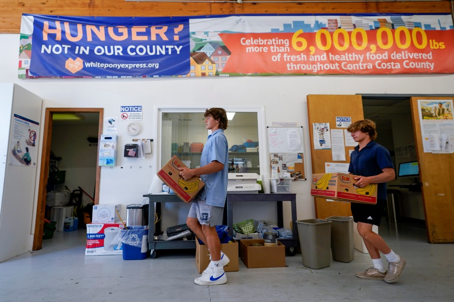 Owen Estee, left, and Zach Appel, right, Acalanes High School Varsity Lacrosse players, carries some of the boxes as they volunteer at the White Pony Express on Tuesday, July 28, 2020 in Pleasant Hill, Calif. Both launched Lacrosse Against Hunger, to offer lacrosse coaching sessions to 7-14 year olds in exchange for a charitable donation to White Pony Express during the COVID-19 pandemic.All money raised goes directly to White Pony Express through Lacrosse Against Hunger