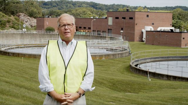 In this undated image taken from video, Danbury Mayor Mark Boughton stands in front of the Danbury Wastewater Treatment Plant in Danbury, Conn., as he announces a tongue-in-cheek move to rename the facility after John Oliver following the comedian