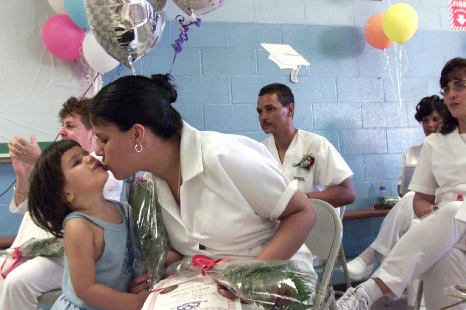Jessica Bernard gets a kiss from 2-year-old friend Shalizee Velez who ran up and surprised Jessica with flowers and balloons during Bilingual CNA Program graduation ceremony at Wilcox Vocational Technical School Friday evening June 23, 2000. Jessica was among the students graduating. Shalizee is the daughter of Angel Velez, Jessica