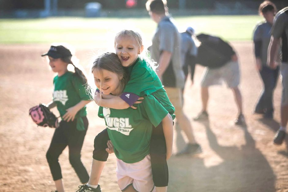 Samantha Allison gets a piggyback ride from teammate Nathalie Voisine after a Wallingford Girls Softball League game last spring. The independent slow-pitch youth league decided this week to cancel its 2020 season due to the coronavirus pandemic. Photo courtesy of Kari Mik
