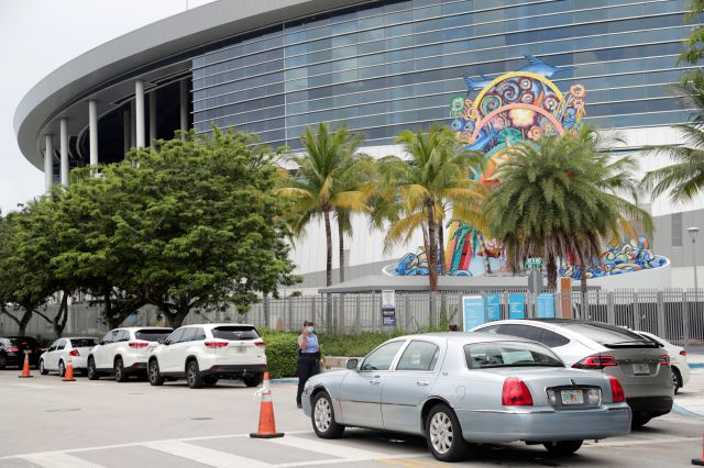 Vehicles pass by the home run sculpture as they wait in line outside of Marlins Park at a COVID-19 testing site during the coronavirus pandemic, Monday, July 6, 2020, in Miami. The long line of cars each morning as players arrive at work provides a reminder of the risks when they leave. Behavior away from the ballpark will be a big factor in determining whether Major League Baseball