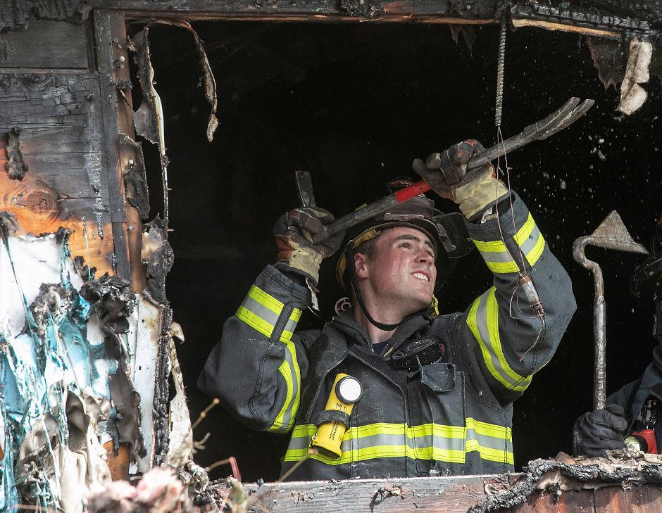 A Meriden firefighter claws at the window frame of a house heavily damaged by fire at 32 Spice Hill Dr., Monday morning, Sept. 28, 2020. Dave Zajac, Record-Journal