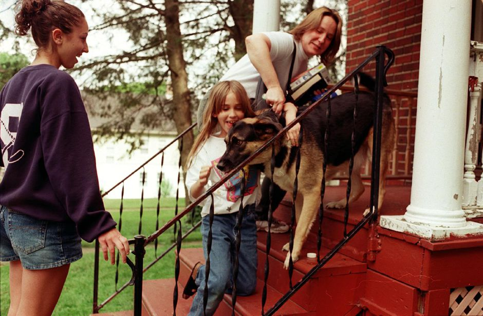 Jill Lemay, 17, left, Allison Ziebka, 9, and Linda Zeibka, attempt to put their dog Chance back into the house after his unexpected escape Monday afternoon on Knowles Avenue in Southington une 19, 2000.