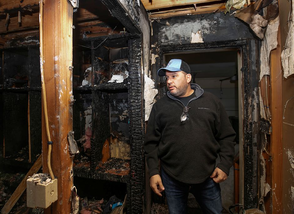 Douglas Papallo looks over the damage to a mud room and hallway inside his residence at 7 Huelstede Lane in Wallingford on Tuesday. Papallo's family escaped the Monday morning fire but three cats were lost in the blaze. The family's dog and and a 20-year-old cat survived the fire. Dave Zajac, Record-Journal