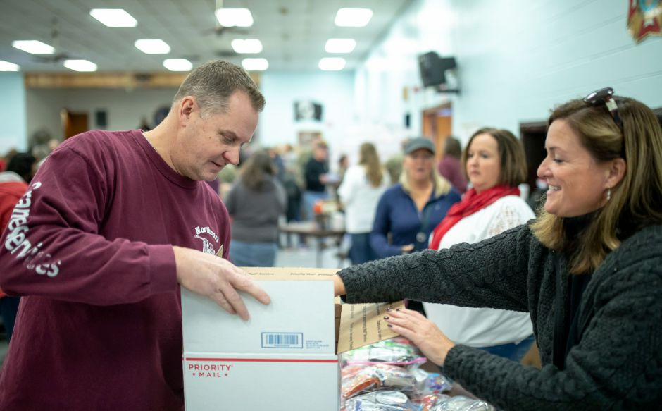Mike Buchholz receives items to sent to soldiers overseas at the New Britain Veterans of Foreign Wars post for the Hero Boxes care package packing day on Nov. 9, 2019. The Berlin-based non-profit sends hundreds of care packages to soldiers serving in war zones each year. | Devin Leith-Yessian/Berlin Citizen