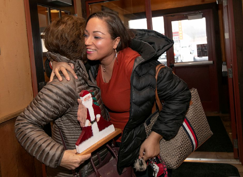 Above right, Kaoutar Tayoubi-Elidrissi, 31, of Meriden, right, hugs her former teacher Mary Lou DiPaola, of North Haven. DiPaola brought along several mementos, including a wooden Santa Claus Tayoubi-Elidrissi gave to her when she was her student.