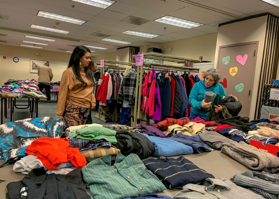 Natalie Gill, a social services worker, talks with residents picking out free coats and winter accessories at the Meriden Senior Center on Friday. Jessica Simms, special to the Record-Journal