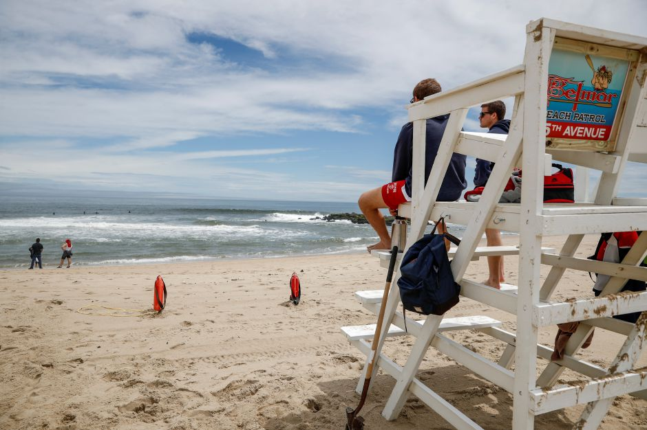Lifeguards keep watch at a mostly empty beach Saturday, May 23, 2020, in Belmar, N.J., during the coronavirus pandemic. (AP Photo/John Minchillo)