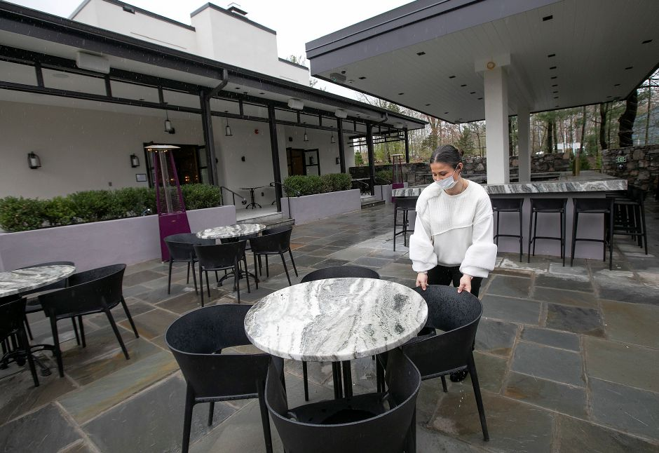 A server, who declined to be identified, straightens up the outdoor patio at Viron Rondo Osteria in Cheshire, Fri., May 1, 2020. Gov. Ned Lamont announced restaurants may be able to reopen outdoor dining on May 20. Dave Zajac, Record-Journal