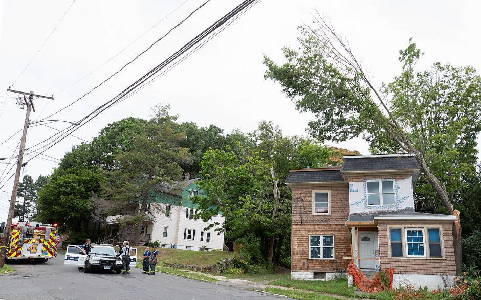 Meriden police and fire personnel confer after a snapped tree fell on a house at 13 Warren St. in Meriden, Tues., Aug. 4, 2020. Dave Zajac, Record-Journal