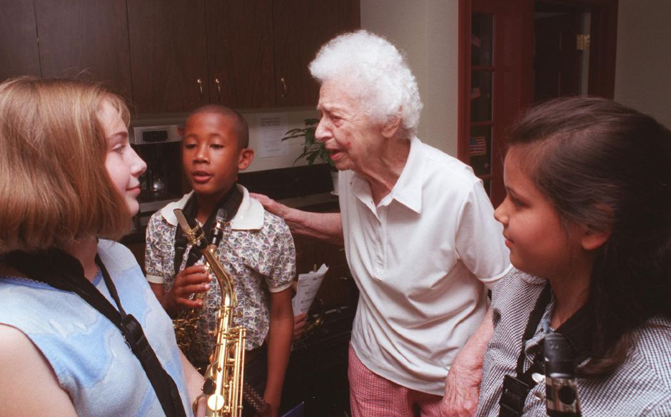 Bearnice Hurley, a resident of The Orchards in Southington, praises Taylor Crofton, left, Braudon Crosby, and Linsey Laporte, all members of the Kelley School Jazz Band after their performance Friday morning at The Orchards June 9, 2000.