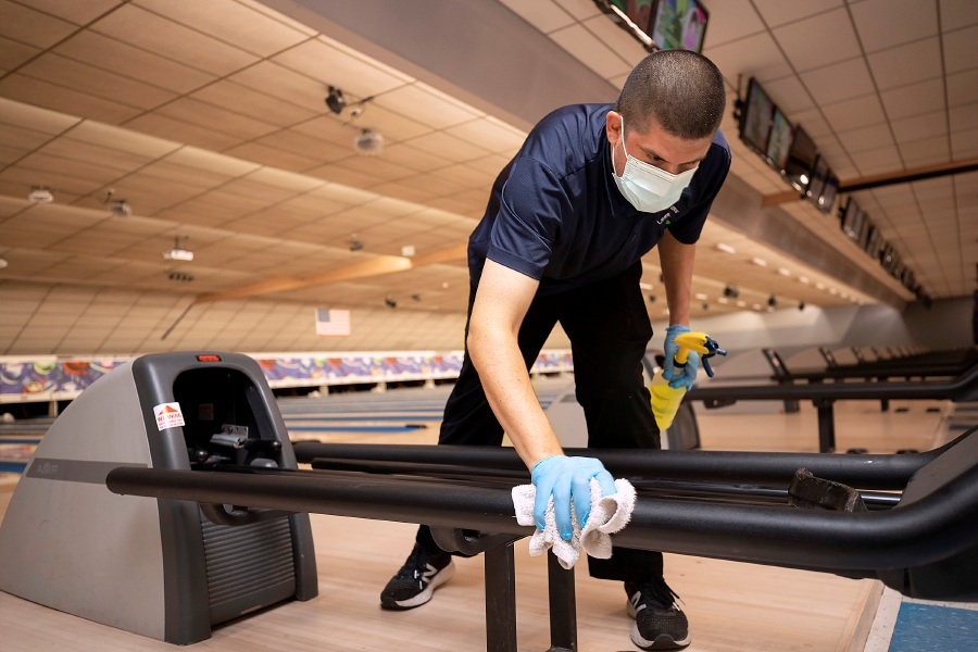 Manager Jason Scagliarini wipes down a ball return between customers at Lessard Lanes, 136 New Britain Ave., Plainville, Wed., Jul. 29, 2020. Most area alleys have opened back up and Lessard Lanes has made many adjustments to make their bowlers feel safe. Dave Zajac, Record-Journal