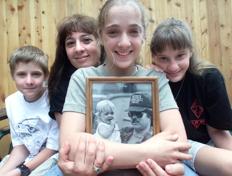 Courtney Gertz (center),13 holds a photo of her as a baby with her father , the late Kenneth Gertz ,Jr. June 11, 2000. Courtney wrote a Father
