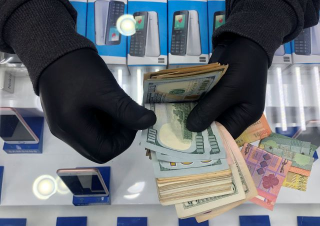 FILE - In this April 28, 2020 file photo, a cell phone shop owner wears gloves as he counts U.S. dollars, in Beirut, Lebanon. A financial meltdown has thrown its people into a frantic search for dollars as the local currency