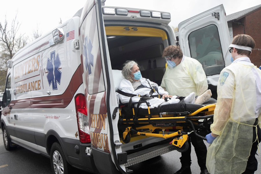 Nereida Diaz, 76, of Meriden, returns home on Thursday, April 30, 2020, after recovering from COVID-19 complications at MidState Medical Center in Meriden. Hunter's Ambulance EMTs Myles DiValentino, left, and Trevor Reitano assist outside her residence on Park Street. Dave Zajac, Record-Journal