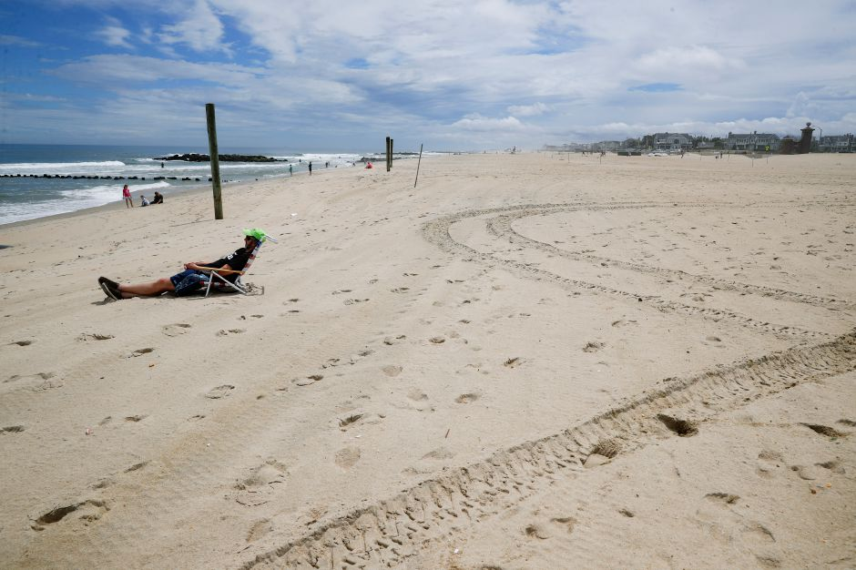 Kevin Heine relaxes on a mostly empty beach Saturday, May 23, 2020, in Belmar, N.J., during the coronavirus pandemic. (AP Photo/John Minchillo)