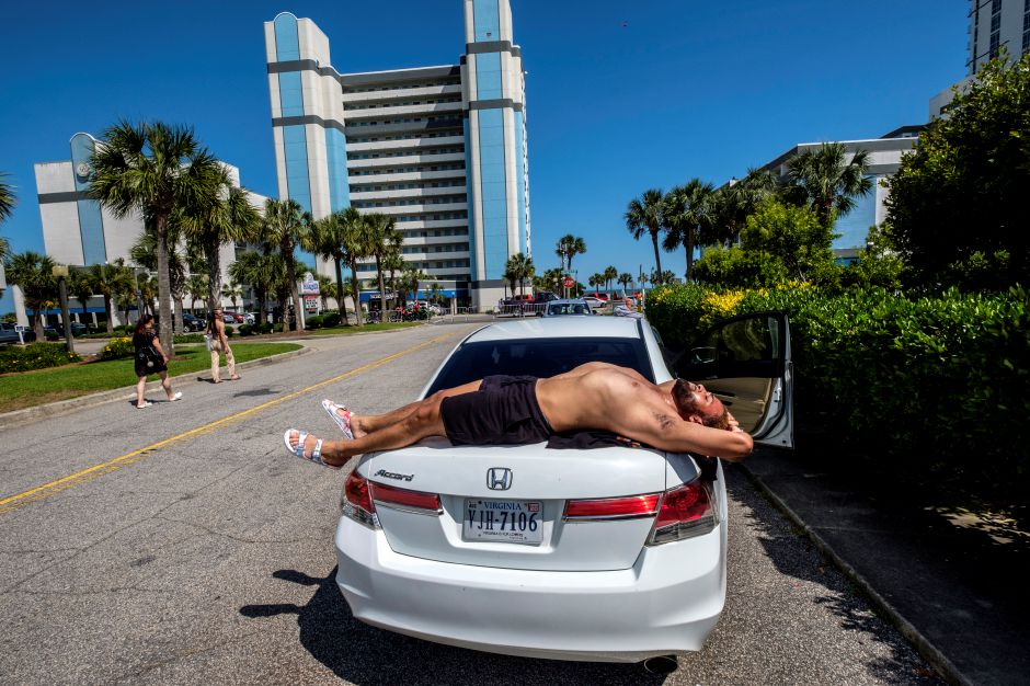 Darien Foxx, of Virginia, sun bathes on the back of his car while he waits on the rest of his party to check into a hotel amid the coronavirus pandemic, Saturday, May 23, 2020, in Myrtle Beach, S.C. (Jason Lee/The Sun News via AP)